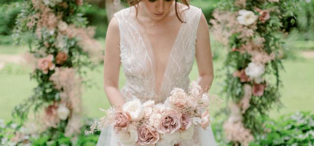 une somptueuse mariée tenant son bouquet, habillée de sa robe rose et blanche devant son arche de cérémonie entièrement fleurie