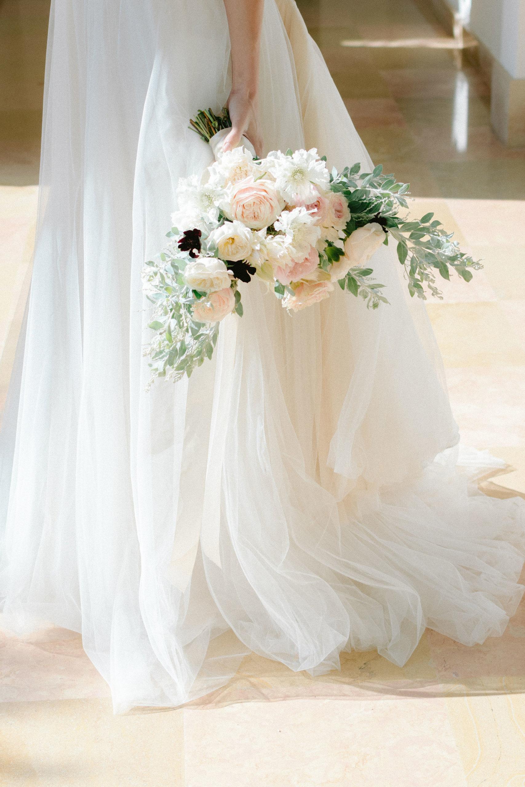 une ceremonie laqué en extérieure avec une arche drapée et des fleurs