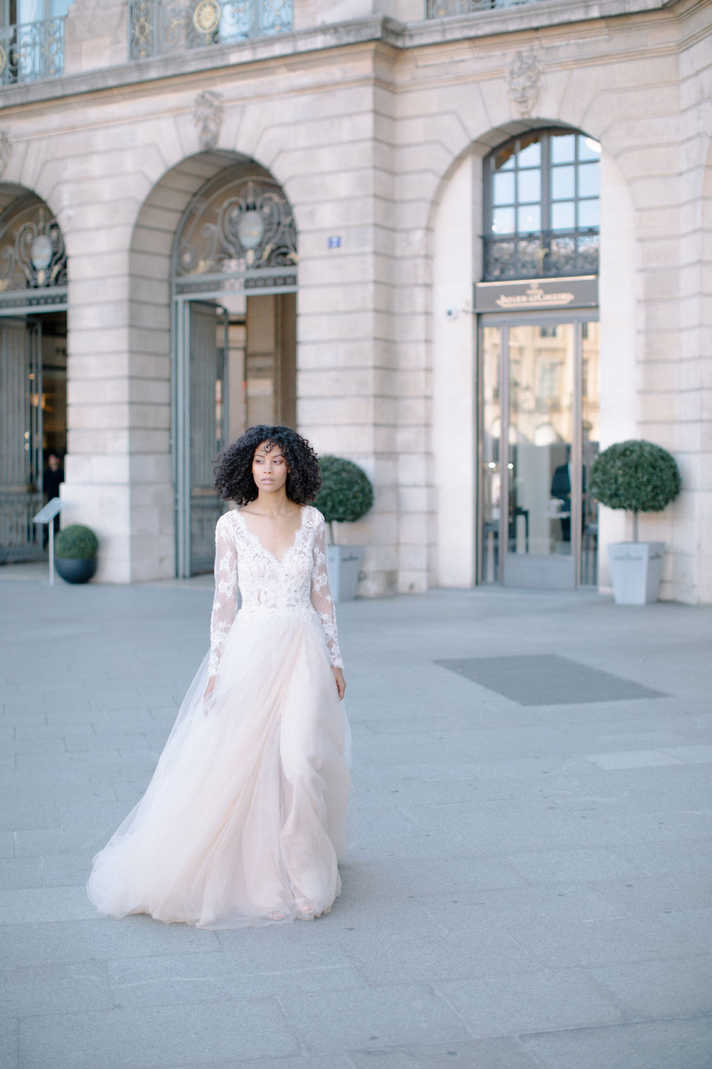 une belle mariée marchant sur la place vendome à paris