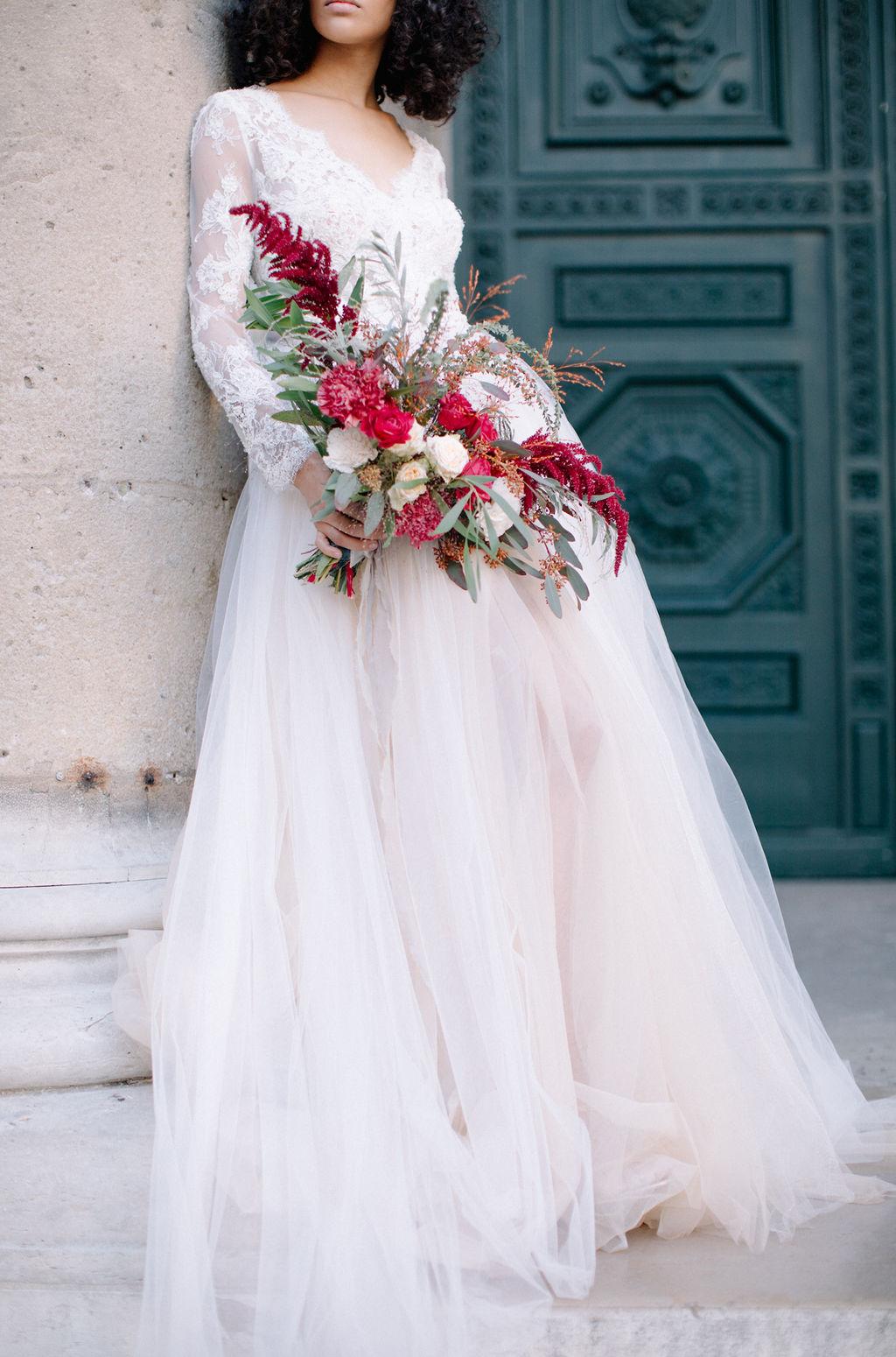 sublime mariée tenant son bouquet à la main, dans une robe ton nude se promenant à Paris